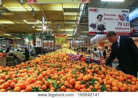 Bucharest Romania 17 January 2017: A man chooses oranges in a supermarket in Bucharest.