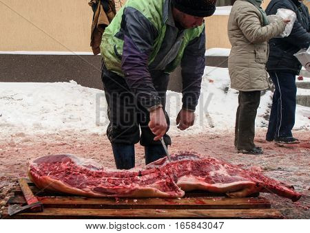 Calugareni Romania December 20 2009: A man is cutting portions of a pig in an animal market in Calugareni. Before Christmas animal breeders are selling and sacrificing their animals in animal markets.