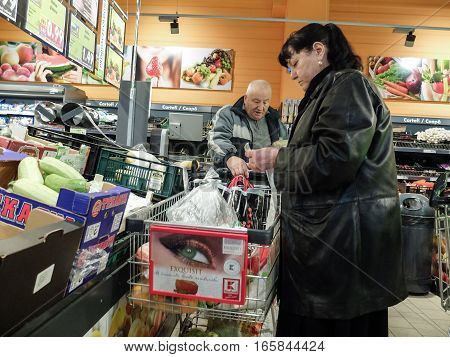 Bucharest Romania December 24 2015: People are putting their products in a cart in a supermarket in Bucharest.