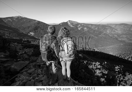 Hikers Standing At The Mountain Peak On A Sunny Day