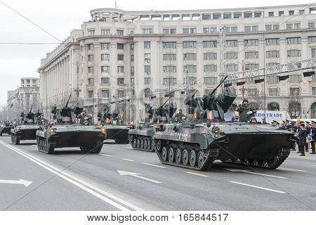 BUCHAREST ROMANIA - November 29 2015: Military on heavy vehicles are marching during a rehearsal for National Day of Romania military parade in Bucharest. More than 3000 soldiers and personnel from security agencies take part in the massive parades on Nat