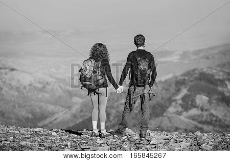 Young Couple Hikers Enjoying The View Of The Mountains.