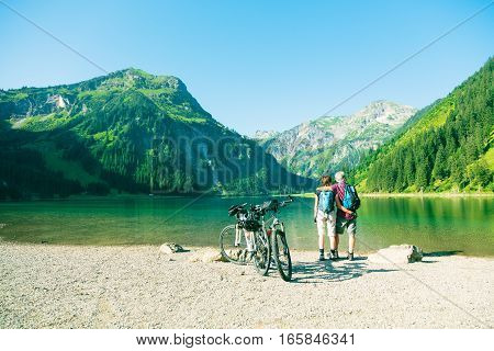 Cycling senior couple taking a break by the lake.