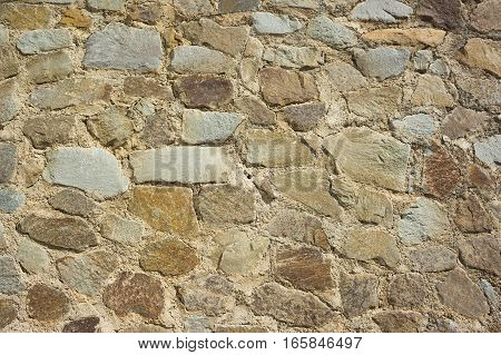 Fragment of a wall stylised under a stone laying a natural stone