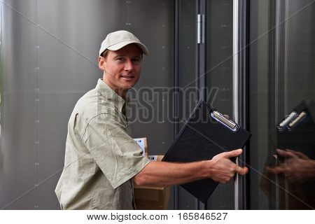 a delivery person is standing in front of a modern building's entrance