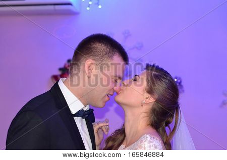 The bride kisses the groom on the nose.
