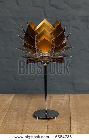 Front view of gold conceptual table lamp on wooden stand on gray brick wall background