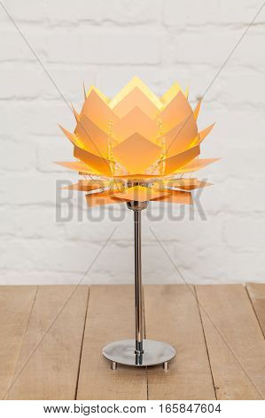 Front view of beige conceptual table lamp on wooden stand on white brick wall background