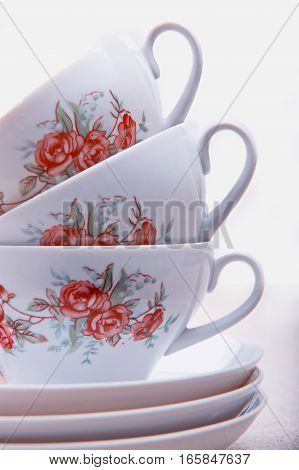 Cups on saucers. In one another. On a white background.