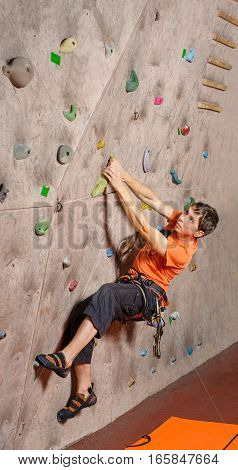 Young man climbing at beginning of route on practical wall in gym bouldering indoors.