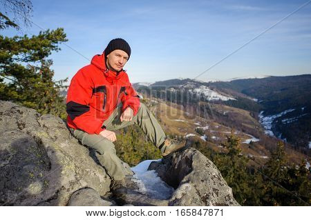 Male Tourist Sitting On Rock On Top Of The Mountain