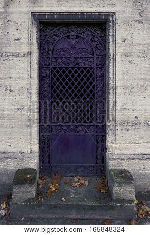 purple iron door with a bat - the closed entrance to an ancient crypt / tomb. The amtosphere is dark. The central ornament is a bat spreading its wings widely in the round arch. Other decorations are grapes, faces and a steel bar pattern.