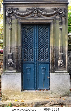 Blue steel door with rectangular frame as entrance to a crypt / tomb. It is ornate with a cross pattern, floral decorations and big vases. The doorframe contains chiseled reliefs of torches carved into the stone.