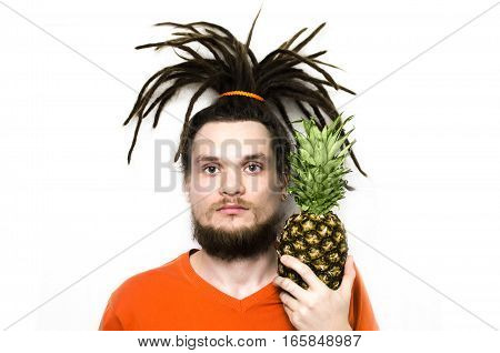 man with dreadlocks with a strange haircut and pineapple in a hand in an orange t-shirt