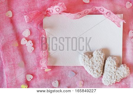Valentine's Day symbols heart shaped cookies and invitation template on pink backdrop