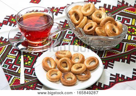 Bagels and cup of tea on the tablecloth with ornaments.