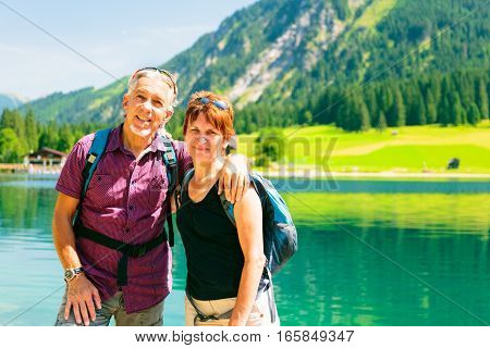 Hiking senior couple with nice lake in the bacground.
