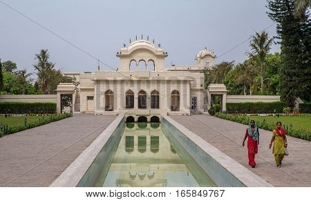 PINJORE, INDIA. June 8, 2009: Pinjore Gardens (Yadavindra Gardens), built for the concubines of the ruler. The Palace reflected in the water. Hindu women walk on the terraces. Pinjore, Haryana, India