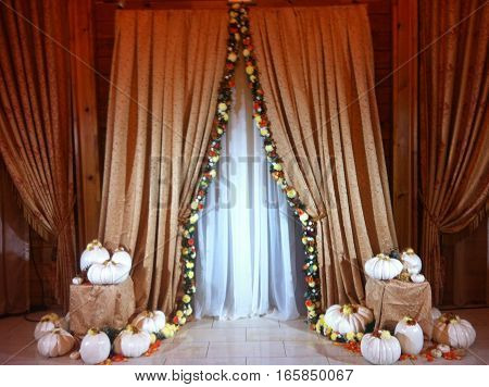 Indoor wedding ceremony setting with pumpkin and