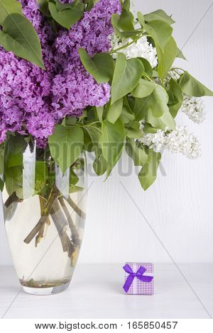 Bouquet Of Lilac In Vase With Purple Gift Box On White Background