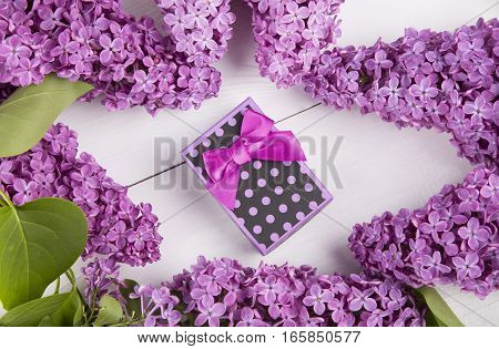 Purple Gift Box Surrounded By Lilac Branches On White Background
