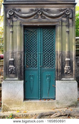 Iron double door with turqoise color, entrance to an old tomb / crypt. Ornate with vases, floral and cross patterns. Chiseled reliefs of torches are carved into the stone frame.