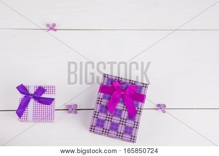 Two Purple Gift Boxes Surrounded By Lilac Flowers On White Background