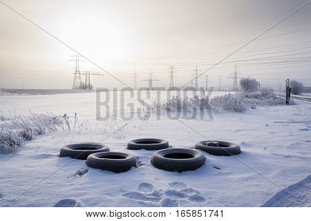 Winter Tires On Snow With Electricity Distribution Plant In Background