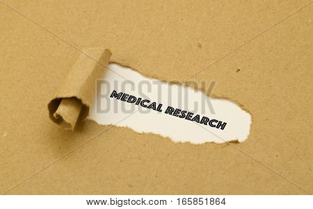 Medical Research word written under torn paper.