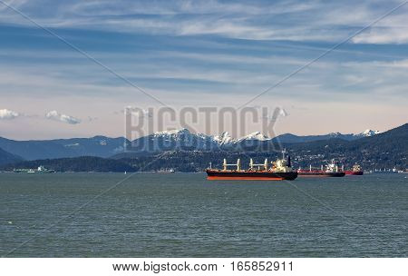 Vancouver harbor, ocean tankers waiting for loading in port on the background scenery of snow-capped mountains