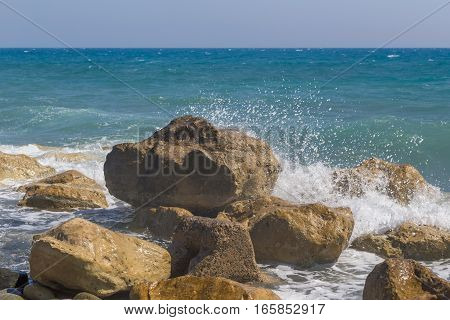 Large rocks with waves crashing and spray. Shot of large rocks with waves crashing onto them. Mediterranean sea in Cyprus.
