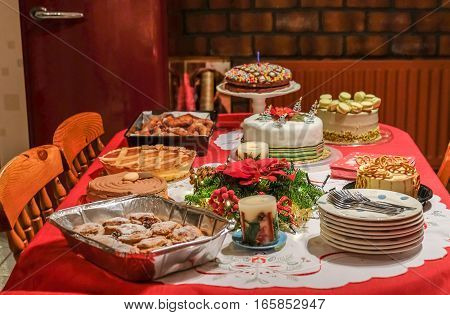 Festive table full of assorted deserts. Selection of cakes dounuts tortes and mince pies set out on a festive table at Christmas time.
