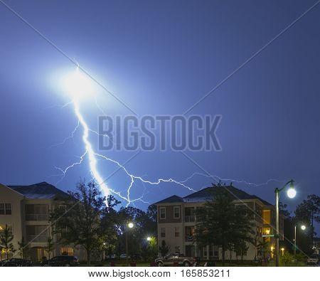Massive blue lightning strike in a neighborhood