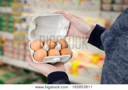 Man holding egg box in supermarket. egg box buy carton man hold checking consumer concept