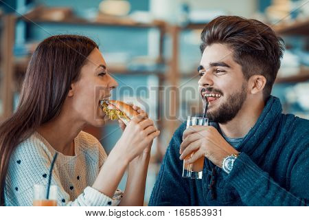 Happy young couple having breakfast in cafeenjoying together.