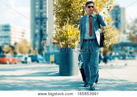 Elegant businessman walking with suitcase outside airport.