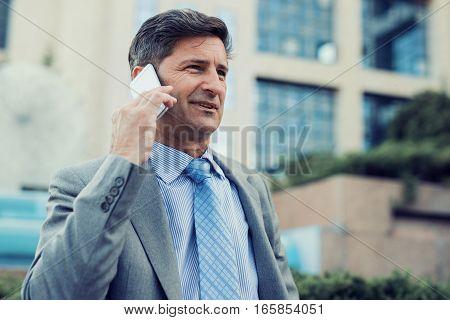 Businessman using smart phone outdoors, close up