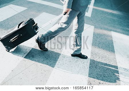 Close up of businessman carrying suitcase while walking on zebra crossing.