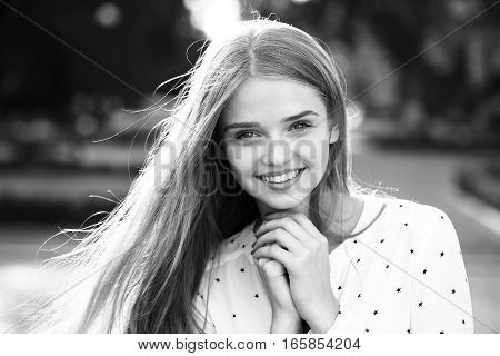 Pretty cute young woman or girl with long blonde hair tender hands in blouse with stars smiling outdoor black and white