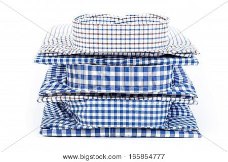 Front view of stack of folded men's classic cotton plaid shirts with long sleeve isolated on white background.