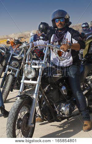 JERICHO ISRAEL - NOV 12 2016: Unidentified Israeli biker on his bike looks at camera whila on a trip in Judean desert.