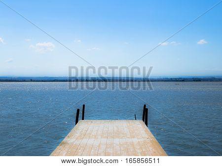 Wooden pier in beautiful lagoon under blue sky in Puglia (Italy)