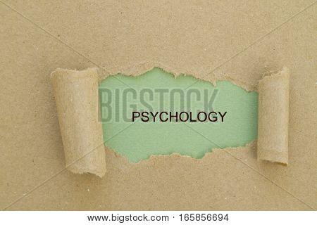 psychology  word written under torn paper .
