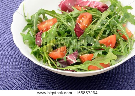 Arugula, sesame and cherry tomatoes with olive oil close-up