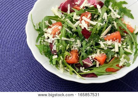 Arugula, moldavian cheese and cherry tomatoes with olive oil close-up