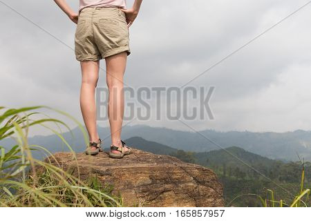 Woman enjoying pristine nature and beautiful view of tea plantations from the top of Small Adams peak near Ella, Sri Lanka. Tracking outdoors tourist adventure.