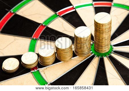 Stacks of golden coin close up on a professional dart board background