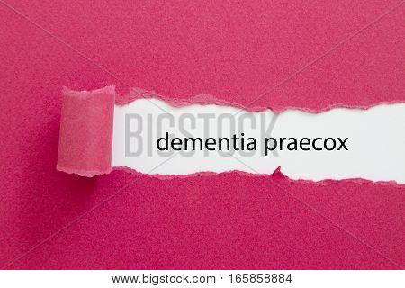 dementia praecox word written under torn paper.