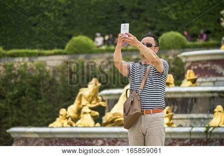 Versailles, France - June 2016: tourist taking selfie in the park of Versailles palace