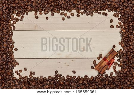 Frame with roasted coffee beans and cinnamon sticks on wood background